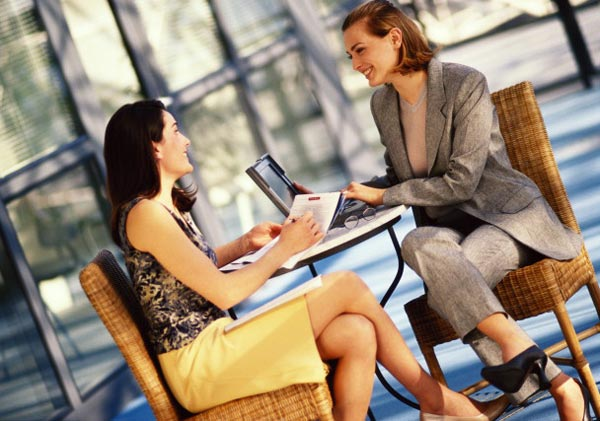 Две женщины сидят за столиком и улыбаются друг другу