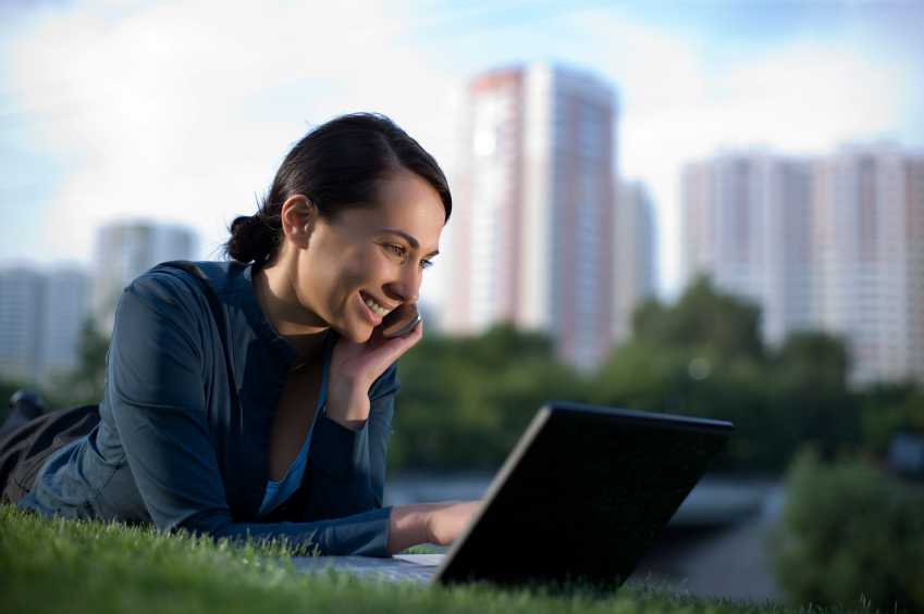 Девушка с ноутбуком лежит на твава на берегу реки и разговаривает по телефону