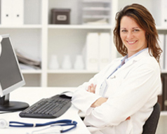 Женщина-врач сидит за столом перед компьютером вполоборота и улыбается