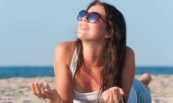 Девушка в белой майке и джинсах лежит на песке у моря, подняв лицо к солнцу