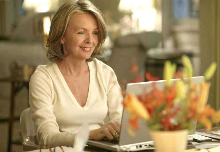 Активная немолодая женщина, довольная жизнью, сидит в кафе с ноутбуком