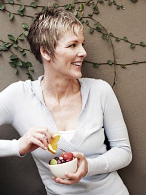 Немолодая женщина улыбается, в руках держит мисочку с фруктами