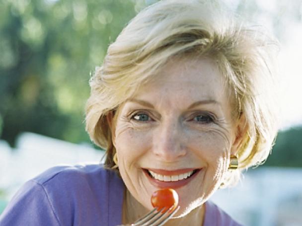 Женщина в возрасте улыбается, есть помидорку