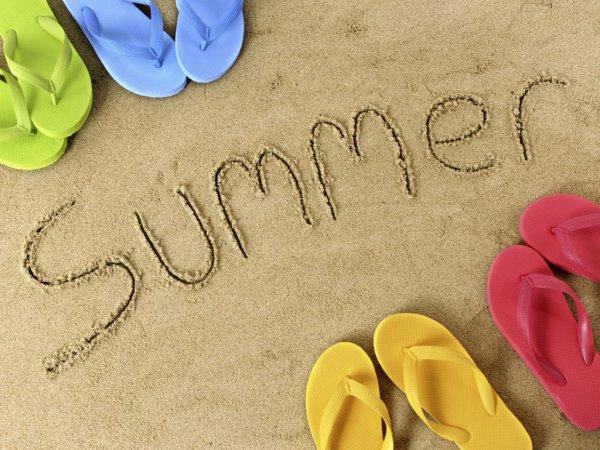 Summer написано на песке и рядом стоят сланцы