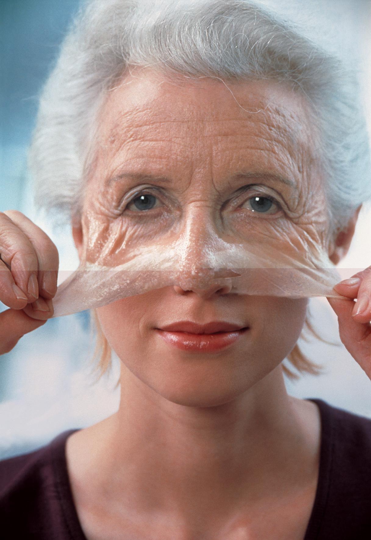 Женщина с морщинами снимает маску, под которой молодое лицо