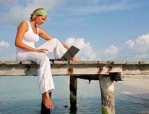 Молодая женщина сидит около моря с ноутбуком