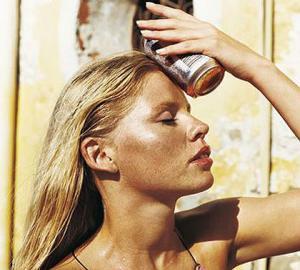 Молодая женщина блондинка прикладывает к голове холодную банку с напитком