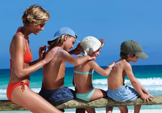 Женщина и три ребеночка мажут друг друга солнцезащитными средствами на фоне моря